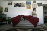 0458 Marleny Navaro, CQ, 30, of Guatemala, right leans against her living-room wall while her...