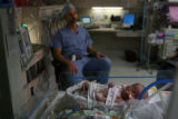 Dr. Steve Rothenberg, (cq) sits behind a sleeping Addison Nicole Whittington in the NICU of...