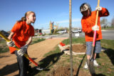 Alexis, 10, and Spencer, 9, Watson, brother and sister, work to finish planting a tree. Spencer is...