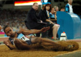 (ATHENS, GREECE-AUGUST 27, 2004) United States' Marion Jones, land into the sand during the...