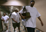 Denver Nugget center Marcus Camby leaves the Pepsi Center Sunday afternoon carrying his trophy as...