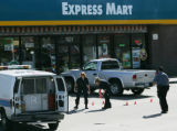 Police investigate a crime scene Sunday afternoon as they outline bullet casings and place small...