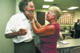Harriet Helmer, 68,  holds the face of a long time friend Tim Cameron, cq, of United Airlines, as...