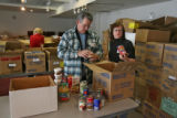 Volunteers Doug Woltemath (cq), left, and Claudia Hiser (cq) sort through a new shipment of...