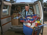 Volunteer Doug Woltemath (cq) unloads a van of donated food from Frontier Valley Elementary School...