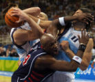 American basketball player Lamar Odom, middle, collides with Argentina's Alberto Luis Scola, #11,...