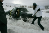 Jessica Dinsmore shovels away snow from her mother Linda Dinsmore's stuck car on Davidson Mesa the...