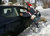 Postal carrier, Shelley Trujillo, 15 year veteran helps push Phil Metzer, of Englewood car with...