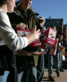 Seniors from the Jim Elliot Schools in Highlands Ranch make a bucket brigade to unload toys from a...