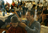 (Denver, Colo., August 15, 2004)  Darian Palacios, 7, of Denver, gets his hair cut by Sid Hugle...