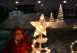 MJM174  Lauren Schaefer, 1, is attracted to a lighted Christmas tree decoration outside the tent...