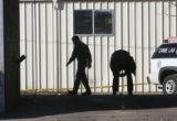Aurora crime scene investigators collect evidence at a car wash Sunday, December 10, 2006, located...