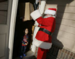 Mail carrier Doug Fischer (cq) delivered two Express Mail packages dressed as Santa Claus to Todd...