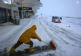 MJM859  Jose Garcia (cq) shovels the sidewalk at DIA Wednesday as a snow storm cancelled incoming...