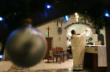 MJM189   Father Mario Ramirez (cq) prepares for communion during Christmas Mass at Our Lady of...
