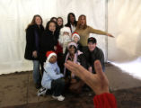 Women and children from a local family shelter have their photo taken with Santa while...
