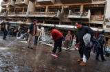 (NYT2) BAGHDAD, Iraq -- Dec. 12, 2006 -- IRAQ-2 -- A group of men wash away the blood and debris...