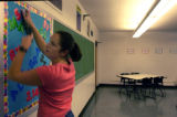 (DENVER, CO., August 27, 2004)  Math teacher Maureen Harcourt works on a bulletin board in her...