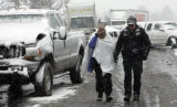 A State Trooper escorts a woman to an ambulance after she was involved in a 25 car pile up, on...