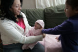 Dolores Duran's (cq) gets her newborn daughter Vivianna Cordova (cq), 11, weeks, dressed to got...