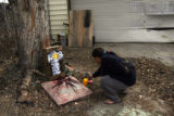 Neighbor Rosanne Sena (cq), fixes a photo at a memorial at the scene of an accident, at 542 E....