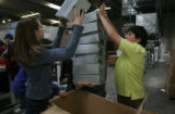 Going for a self proclaimed record, Megan Eldredge, (cq), left, places the 8th box atop the hands...