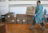Specialist Ben Miller, (cq), a medical lab technician, carries a filled box of blood to the stack...