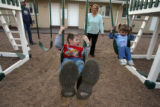 DLM2016  Andrea Thurber pushes her daughter, Brianna, 2, and son Andrew, 5,  on playground swings...