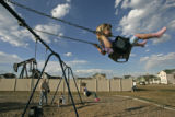 BG0173 Mattea Murphy, 3, swings in a park along side an oil pump in the Summit View neighborhood...