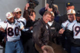Quarterback John Elway dances across the stage pretending to play an air guitar during his...