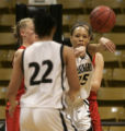 Harrison High School center Alystia Moore passes the ball past Glenwood Springs defenders in the...