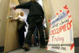 MJM362 Anti-war protester Carolyn Bninski, left, holds the door to Congressman Mark Udall's...