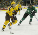 MNPB107 - Minnesota defenseman Erik Johnson skates in with the puck as North Dakota's Darcy Zajac...