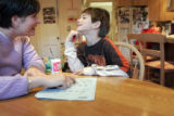 Mandy Koskinen (cq) helps her son Sam (cq), 5, with his homework, while her other son, Jack (cq)...