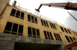 ( DENVER COLO. 8/18/04   A crane unloads concrete blockon the roof of new apartment units at 9th...