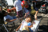 Evangelyn Garcia (cq) 2 1/2, rests in a cart after a day of shopping as her brother Estephan...