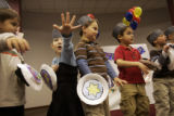 Arielle Fey, 5, shows her age to the audience during Temple Sinai's Chanukah celebration...