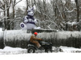 Rocky Brougham (cq) clears snow from his Luckylure  Christmas tree lot on Colo. 73 Wednesday...
