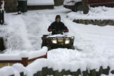 Kimberly Proch (cq) clears snow from the driveway of her Alpen Way Chalet Bed and Breadfast on...