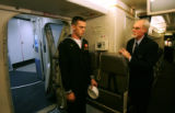 Navy Hospital Corpsman John Dragneff (cq) talks with flight attendant Bill Multhauf as he boards...