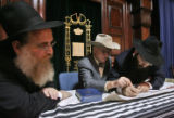 Rabbi Yisroel Engel (cq), left, watches as honored guest Jack Grynberg (cq), center, fills in the...