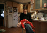 Mandy Koskinen holds her youngest son, Will, 11 months, in the kitchen of their Denver Square home...