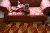 MJM493 Hawa Musa, 2, lays on the couch in her parents, Denver apartment Tuesday.  Her father, Amir...