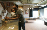 "BG0141 Trevor Pryce listens to music with his 13 month old son Trevor ""Frizzy"" Pryce III..."