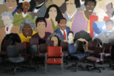 Empty chairs are stored in a classroom inside  Manual High School in front of a mural depicting...