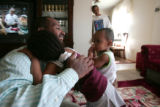 Nur Negawo (cq) a Denver area taxi driver, hugs his daughter Khadija, 3 and son Meira, 15 months,...