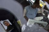 (DENVER, Colo., August 30, 2004) Ahmed Odawaay, Somalia, studies in his car while waiting on line....