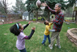 Asha Romeo, 8, left, Dante Seifu Romeo, age 6, center, play football with their dad, Rick Romeo,...