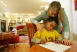 Karen Romeo (cq) kisses her son, Dante Seifu, 6, while he draws a picture in their home in Boulder...