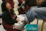 Lisette Williams, (cq), left, laughs enjoying her job as she applies lotion to the feet of Lee...